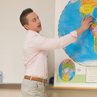 Teacher points to map in the classroom in front of his students.