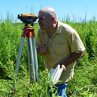 man using surveying equipment in a field